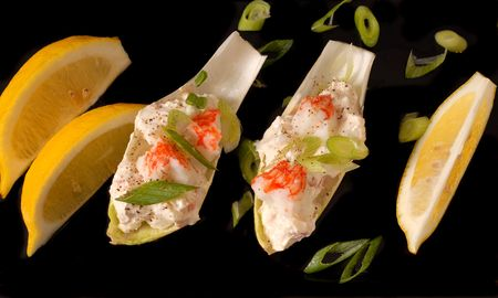 scallions: Crab salad on endive leaves with lemon and chopped scallions on black platter
