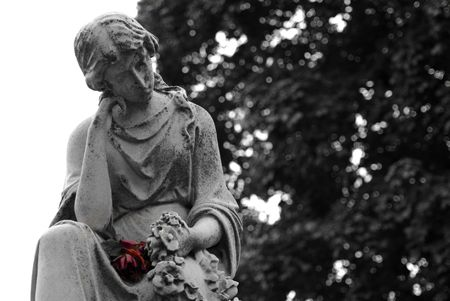 gravesite: Black and White Granite statue of woman holding a colored red rose at gravesite