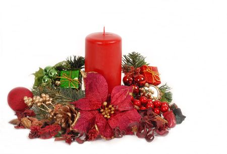 Red Christamas candle in poinsettia setting with holly, evergreen branches isolated on white Stock Photo