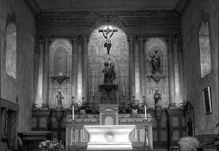 Black and white image of an 18th Century Mission Church awash with glowing light
