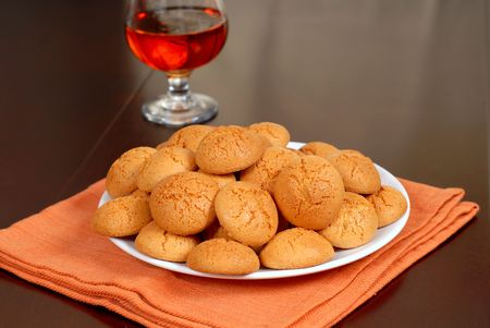 amaretto: A plate of crisp Amaretti cookies resting on an orange napkin with a snifter of Amaretto in background