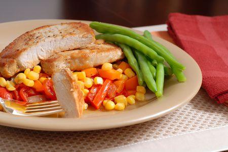 green beans: Un delicioso plato de chuletas de cerdo sobre una cama de ma�z, pimientos y cebolla con jud�as verdes Foto de archivo