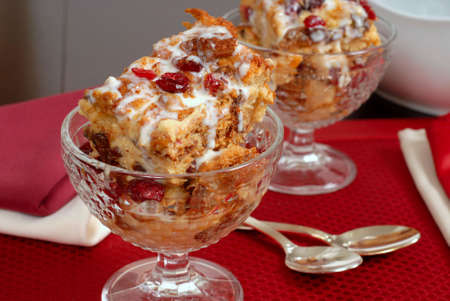 amaretto: Two crystal goblets filled with Italian Panettone cranberry bread pudding with Amaretto cream sauce resting on red placemat with sauceboat in background