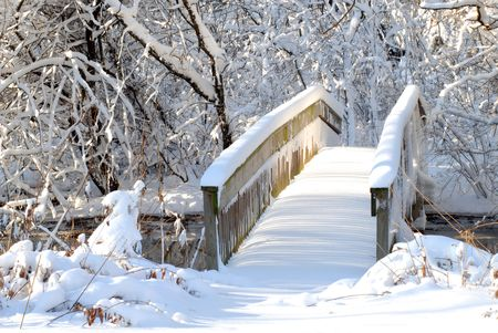A bridge over a stream following a heavy snow in a wooded setting Stock Photo
