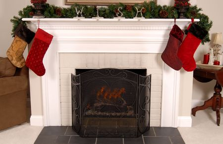 White fireplace decorated with stockings and pine for Christmas Stock Photo