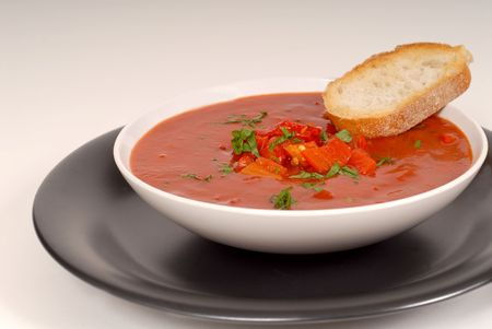 Tomato, red pepper, basil soup in white bowl with bread on a light gray background