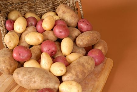 russet: Russet, red and white potatoes spilling out of a basket