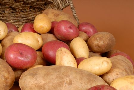 russet: A closeup of russet, red and white potatoes spilling out of a basket