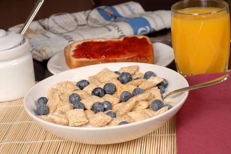 Bowl of wheat cereal with blueberries, toast, orange juice and newspaper photo