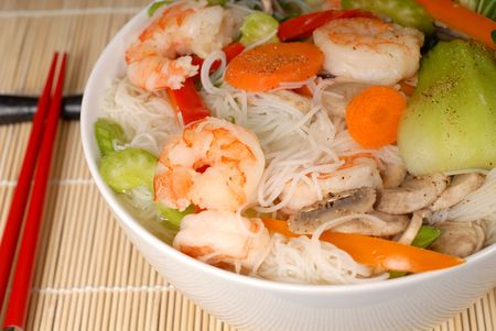 Udon noodles with vegetables and seafood closeup