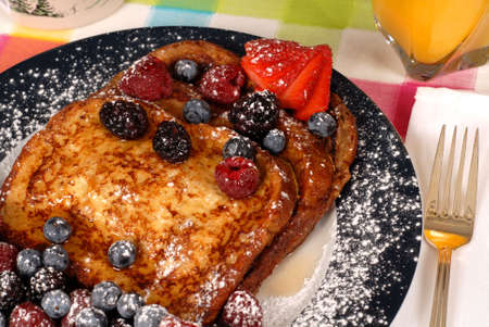 Plate of french toast with fruit and maple syrup closeup photo