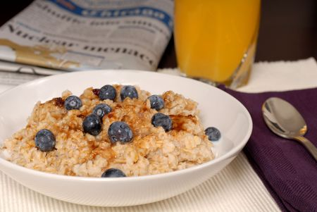 A bowl of oatmeal with brown sugar and blueberries