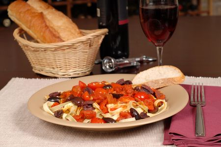 Plate of pasta puttanesca with wine and bread photo