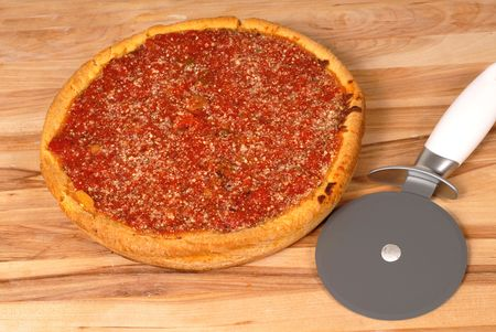 Chicago style deep dish pizza on a cutting board with cutter photo