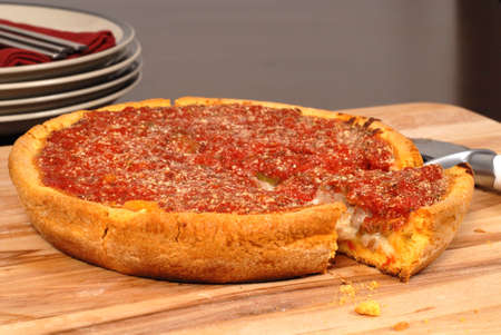 A Chicago style deep dish pizza with a piece cut out photo