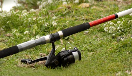 fishing pole: A fishing pole and spinning reel resting on the grass