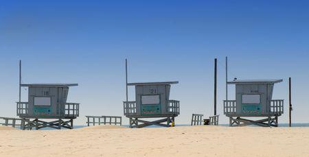 Three wooden lifeguard shacks on Venice Beach, California photo