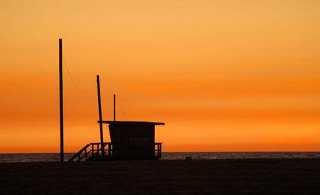 Lifeguard shack on a beach against a golden sunset photo
