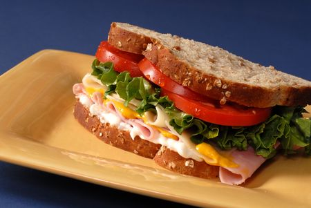 ham and cheese: A ham, cheese, lettuce and tomato sandwich on yellow plate