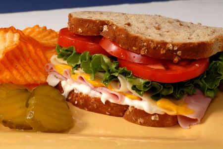 A ham, cheese, lettuce and tomato sandwich with pickles and chips photo