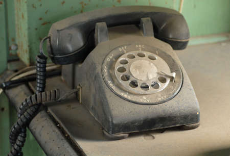 rotary dial telephone: Viejo polvo rotativo tel�fono en reposo sobre una mesa
