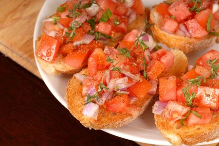 A plate of tomato and onion bruschetta with thyme on cutting board Stock Photo