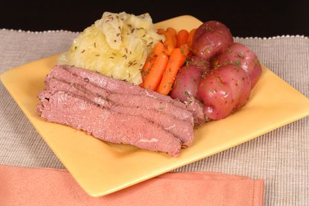 A corned beef and cabbage dinner with potatoes and carrots photo