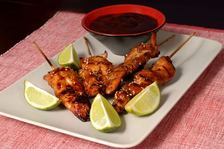 Grilled chicken satay with limes and sesame seeds with a honey BBQ dipping sauce