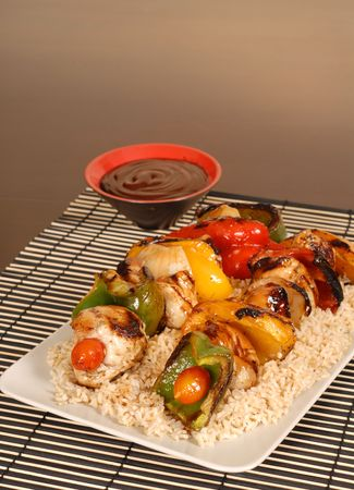 bbq sauce: A platter of chicken kabobs on rice with honey BBQ sauce