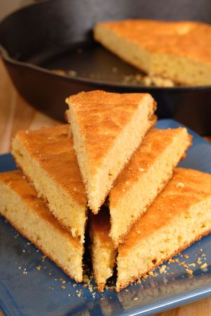 A stack of cornbread on blue plate with black skillet in background