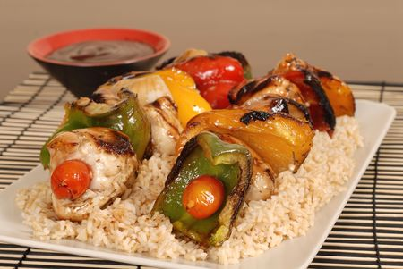 Two chicken shish kabobs on brown rice with dipping sauce Stock Photo - 889743