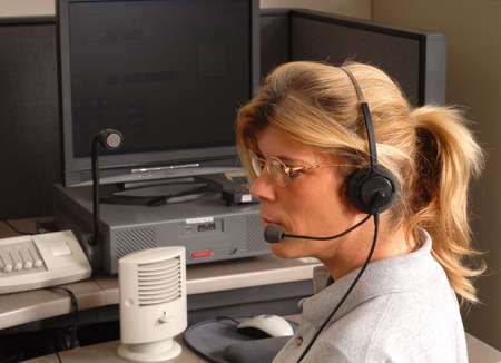 A police dispatcher sitting at a dispatch console Stock Photo
