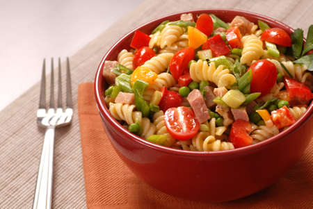 A bowl of pasta salad in a red bowl