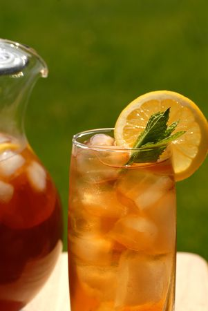 iced tea: A glass of iced tea with a pitcher of tea alongside