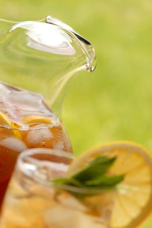 A pitcher of iced tea with glass of iced tea in foreground photo