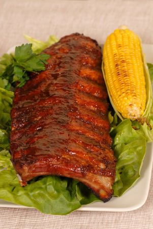 A slab of ribs resting on lettuce with an ear of roasted corn photo