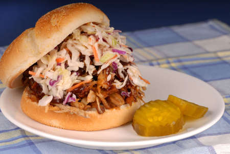 Pulled pork sandwich with cole slaw and pickles photo