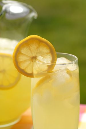 A pitcher and a glass of lemonade with lemon slices Stock Photo