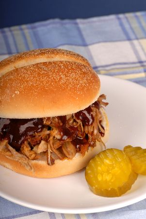 A pulled pork sandwich with pickles on a white plate Stock Photo