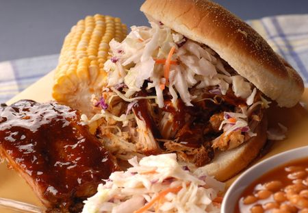A pulled pork sandwich with cole slaw, beans and corn photo