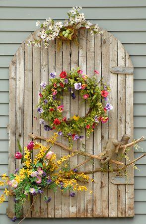 weather beaten: Meteo battuto legno con viti e fiori su un muro Archivio Fotografico