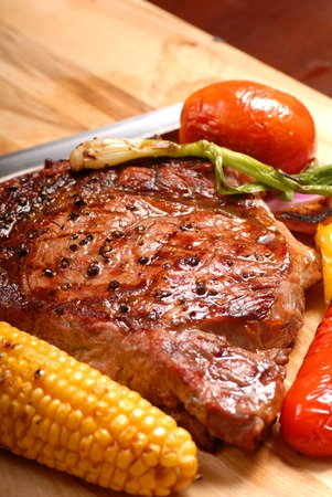 seasoned: Grilled ribeye steak with roasted vegetables and a knife