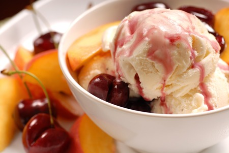 A bowl of ice cream with cherries and peaches