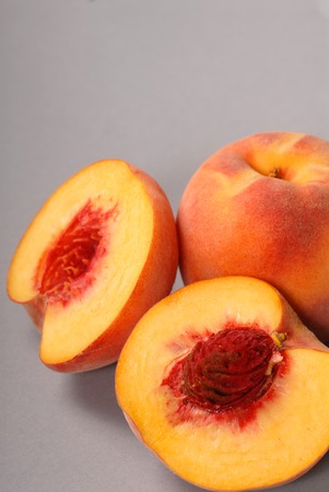 two and a half: Two fresh peaches, one cut in half