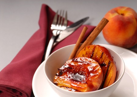 Grilled peaches with raspberry sauce, cinnamon sticks with a peach in the background