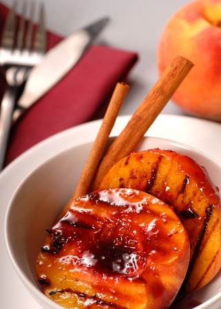 A Grilled peach with raspberry sauce, cinnamon sticks with a peach in the background Stock Photo