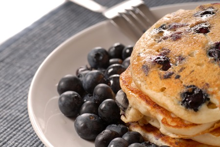 A plate of pancakes with fresh blueberries and syrup Stock Photo