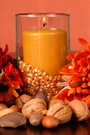 A candle in an autumn setting surrounded with nuts and flowers photo