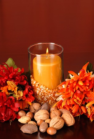 A candle in an autumn setting surrounded with flowers and nuts photo