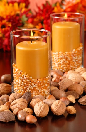 Candle in an autumn setting with corn and nuts photo
